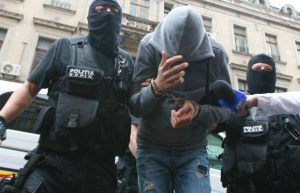 Suspect escortat de mascaţi la audieri